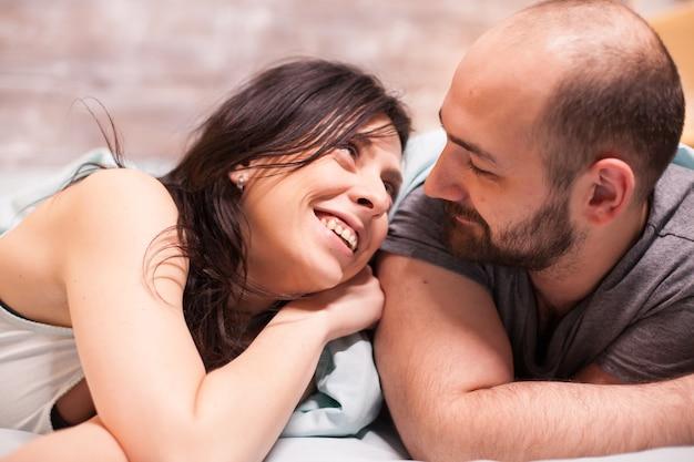 夫を見ながら笑っているパジャマ姿の美女。