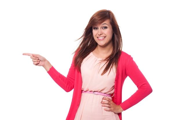 Красивая женщина в розовой одежде, указывая на копию пространства