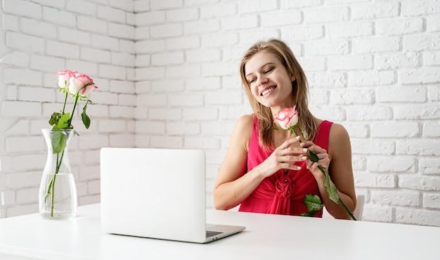 彼女の手にバラを持ってオンラインでデートピンクのドレスの美しい女性