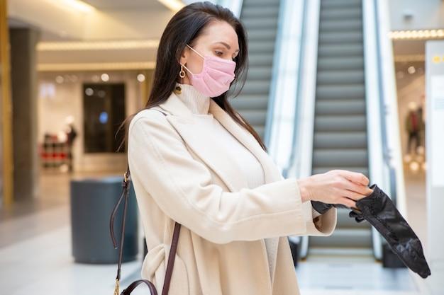 에스컬레이터로 공공 장소에서 가죽 장갑을 끼고 분홍색 의료 마스크를 쓴 아름다운 여성