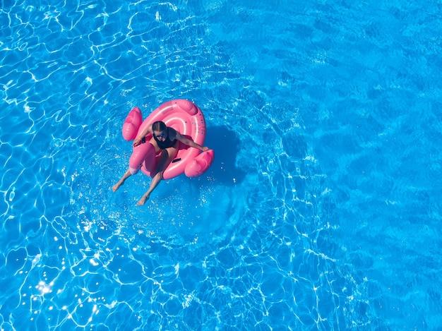 호텔에 플라밍고 수영장이 떠 있는 수영장에서 아름다운 여성