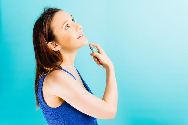 Красивая женщина в профиль, применяя духи с синим фоном концепции красоты парфюмерии