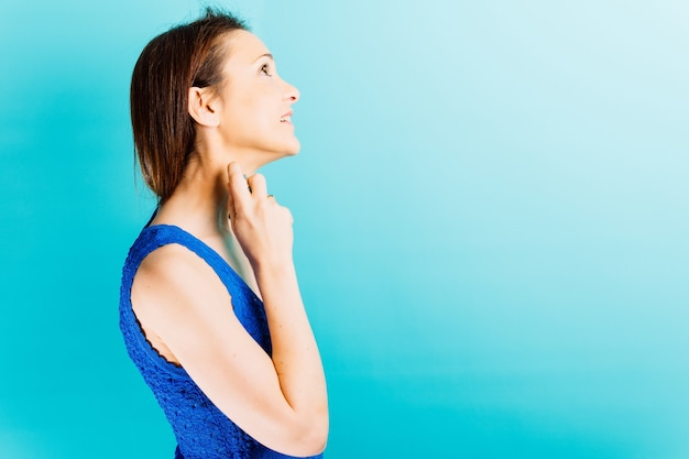 Красивая женщина в профиль, применяя духи с синим фоном