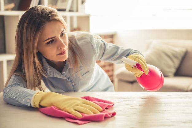 Красивая женщина в защитных перчатках использует распылитель.