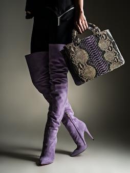 보라색 높은 부츠에서 아름 다운 여자입니다. 유행 소녀는 세련된 보라색 가죽 가방을 보유하고 있습니다. 매력적인 세련된 개념. 미술. 모델은 쇼핑 후 산책합니다.