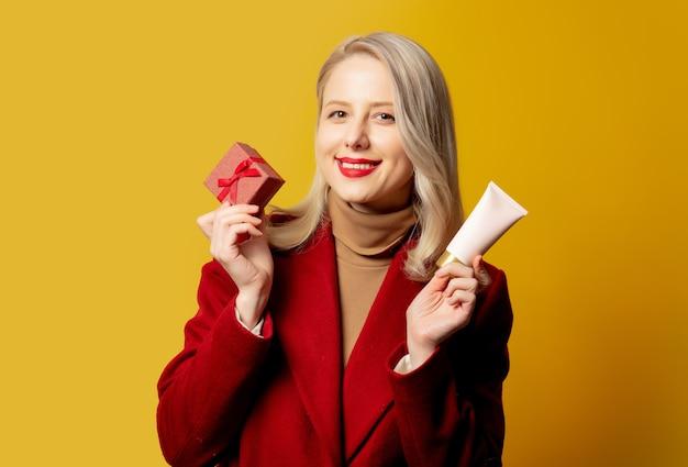 黄色の壁にギフトボックスとクリーム色のチューブと赤いコートの美しい女性