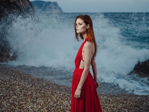 빨간 드레스 해변 바다 풍경 파도에 아름 다운 여자.