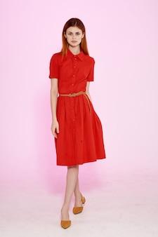 赤いドレスファッションエレガントなスタイルの孤立した背景の美しい女性。高品質の写真