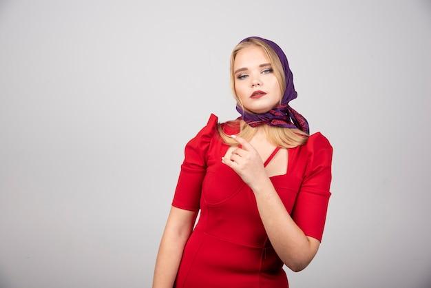 Красивая женщина в красном платье, глядя на камеру.