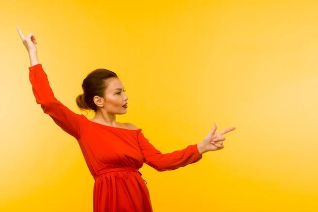 노란색 배경에 손가락을 가리키는 빨간 드레스에 아름 다운 여자