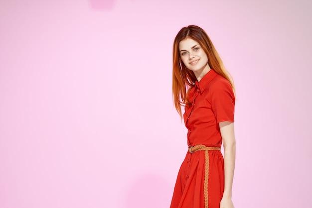 魅力的な外観のピンクの背景をポーズする赤いドレスの美しい女性。高品質の写真