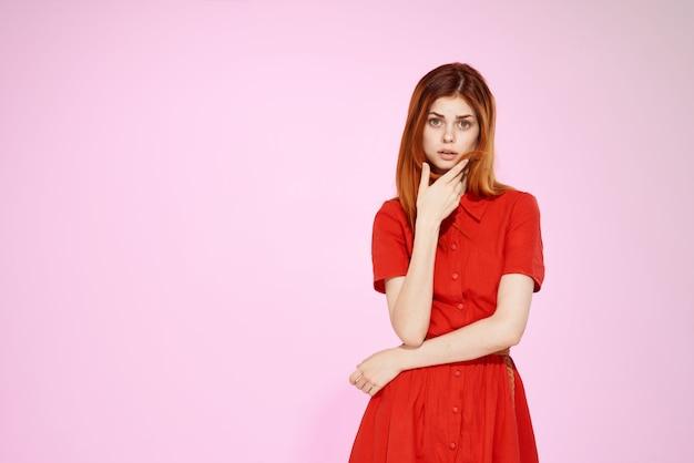 魅力的な外観のピンクの背景をポーズする赤いドレスの美しい女性