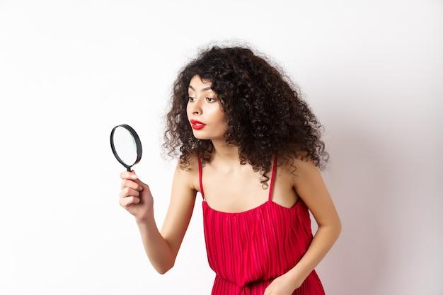 何かを探している赤いドレスを着た美しい女性、虫眼鏡を通して脇を見て、白い背景に立っています。