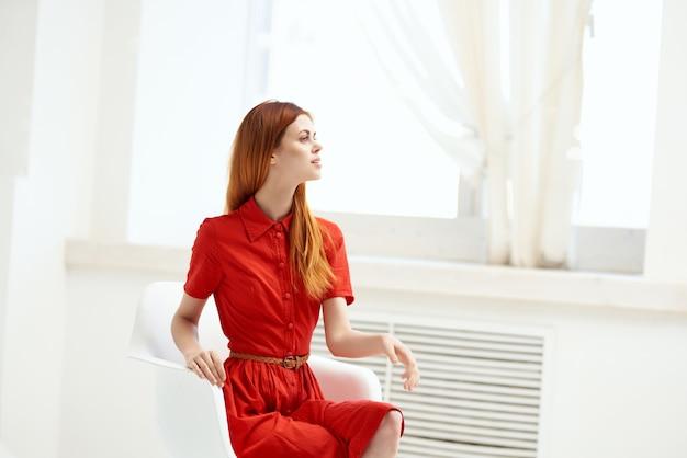우아한 스타일 창 근처에 앉아 빨간 드레스에 아름 다운 여자. 고품질 사진