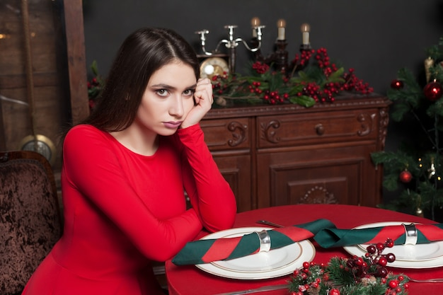 Красивая женщина в красном платье ждет за столом в ресторане с богатым интерьером.