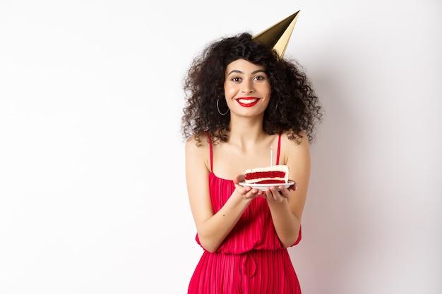 赤いドレスを着た美しい女性、パーティーハットを身に着けて誕生日を祝う、b-dayケーキを保持し、願い事をする、カメラに微笑んで、白い背景の上に立っています。