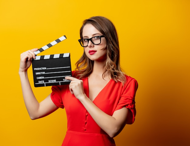 Красивая женщина в красном платье с с 'хлопушкой'
