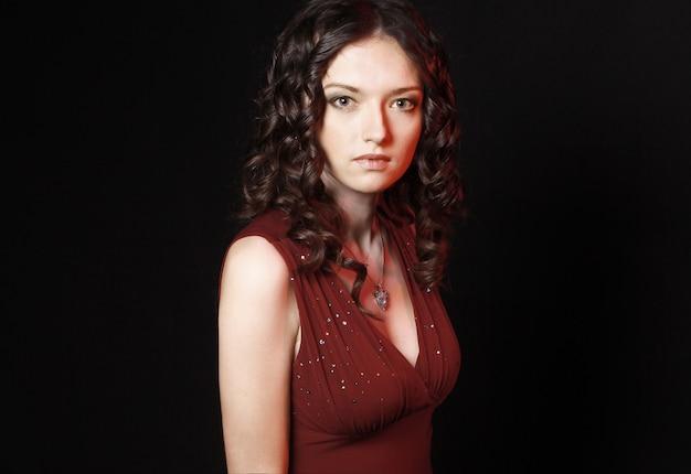 검은 벽에 .isolated 저녁 메이크업 빨간 드레스에서 아름 다운 여자