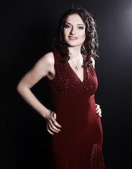 黒い壁に隔離のイブニングメイクと赤いドレスの美しい女性