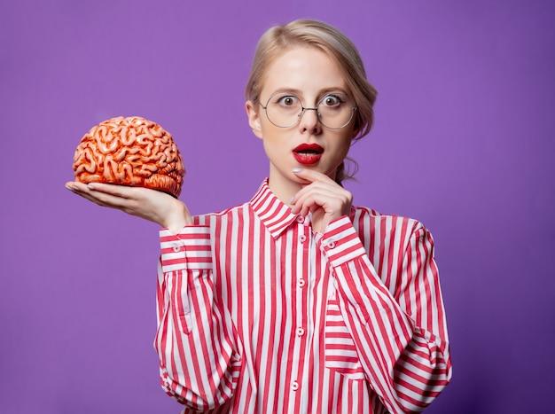 Красивая женщина в красной полосатой рубашке держит человеческий мозг Premium Фотографии