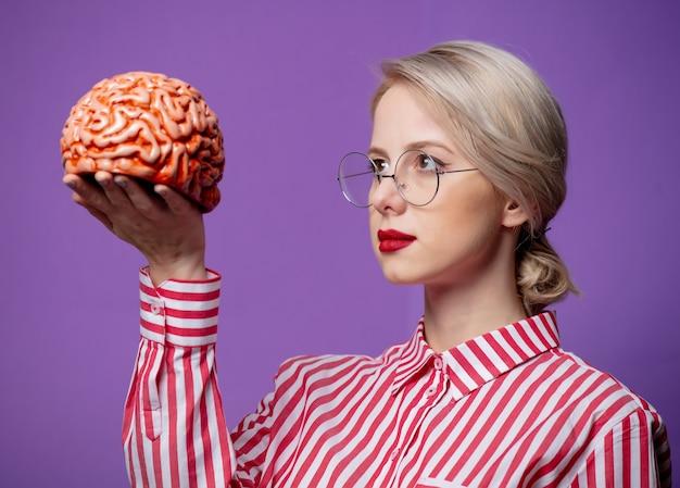 Красивая женщина в красной полосатой рубашке держит человеческий мозг