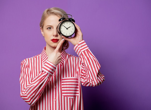 알람 시계와 함께 빨간색 줄무늬 셔츠에 아름 다운 여자