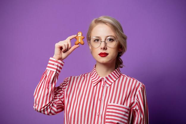 Красивая женщина в красной полосатой рубашке с маленьким пряничным человечком