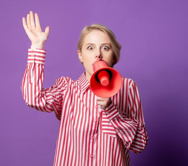 メガホンと赤い縞模様のシャツの美しい女性