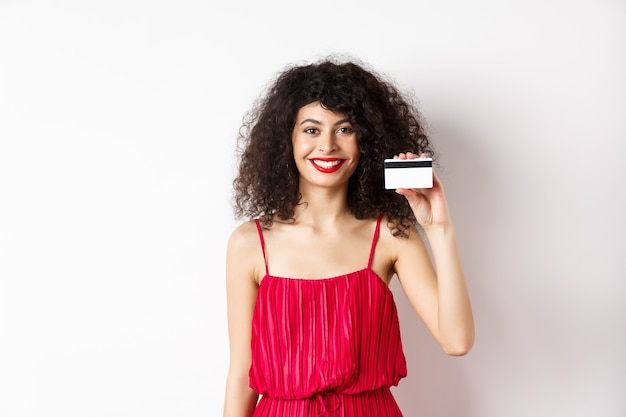赤いトレンディなドレスとメイクの美しい女性、プラスチックのクレジットカードを表示し、笑顔、オファーをお勧めし、白い背景の上に立っています。