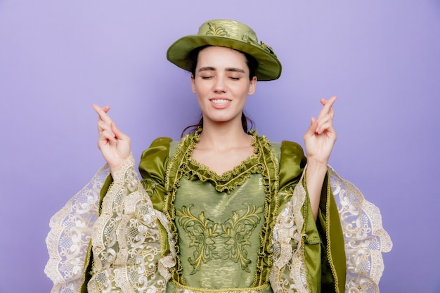 ルネッサンスのドレスと帽子の美しい女性は、青の指を交差する希望の表現で幸せで前向きな願い事をします