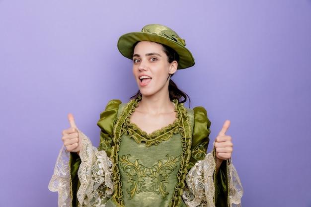ルネッサンスのドレスと帽子の美しい女性は、青に親指を元気に見せて幸せで前向きな笑顔