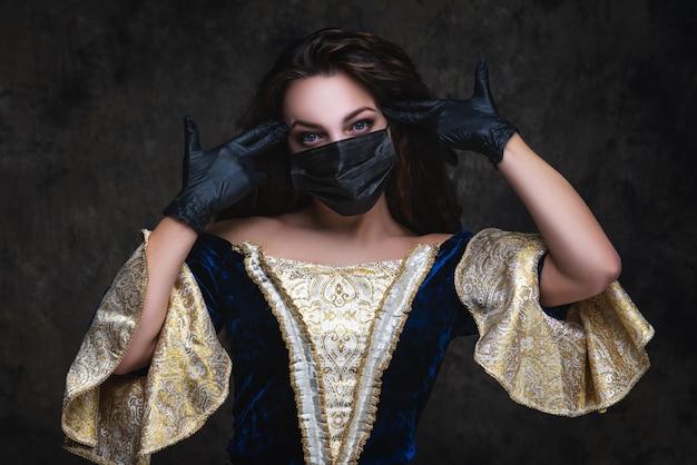 ルネッサンスドレス、フェイスマスクと手袋、コロナウイルス、covid-19保護コンセプトの美しい女性。