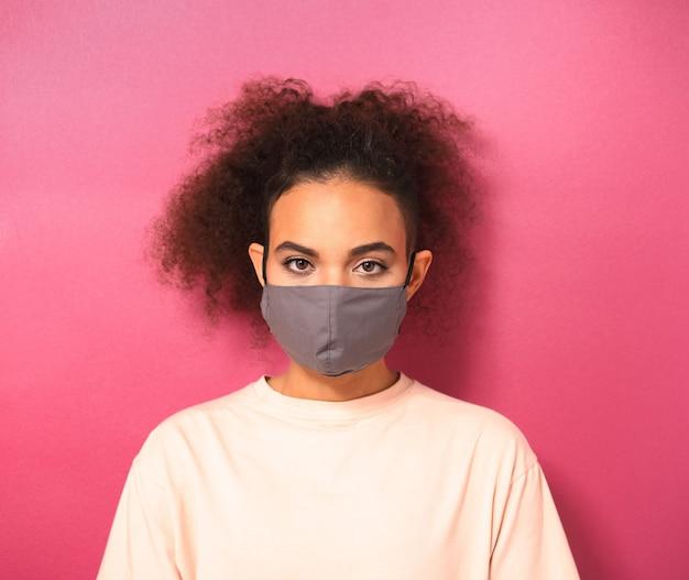 분홍색 벽에 고립 된 코로나 covid-19 및 sars cov 2 감염으로부터 다른 사람을 방지하기 위해 가벼운 복숭아 티셔츠를 입고 재사용 가능한 얼굴 마스크의 아름다운 여인