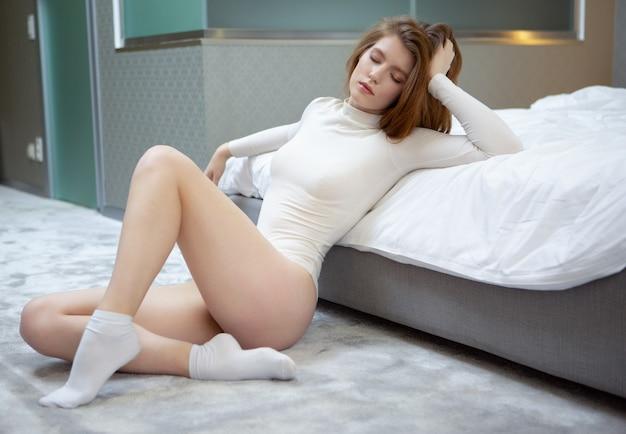 눈을 가진 섹시한 흰색 bodysuit에서 아름 다운 여자는 침대에 기대어 바닥에 앉아 폐쇄