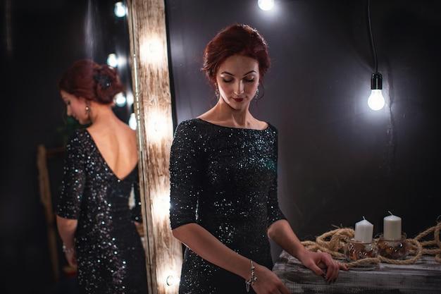 光沢のある黒い鏡の横に立っている光沢のある黒いイブニングドレスで美しい女性