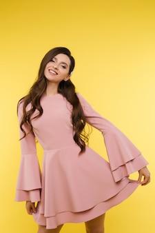 짧은 분홍색 드레스와 유행 헤어 스타일에서 아름 다운 여자