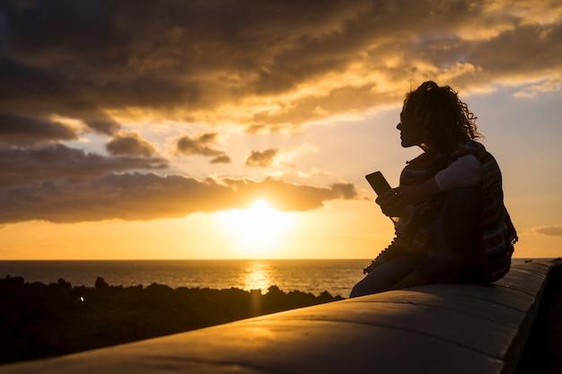 긴 돌 beanch에 앉아 technolofy 모바일 스마트 폰을 사용하여 바다에 황금 놀라운 일몰 동안 실루엣에서 아름 다운 여자. 휴가 쓰기에 좋은 여가 친구