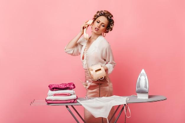 Красивая женщина в шелковой одежде смотрит на одежду и гладильную доску, разговаривает по телефону