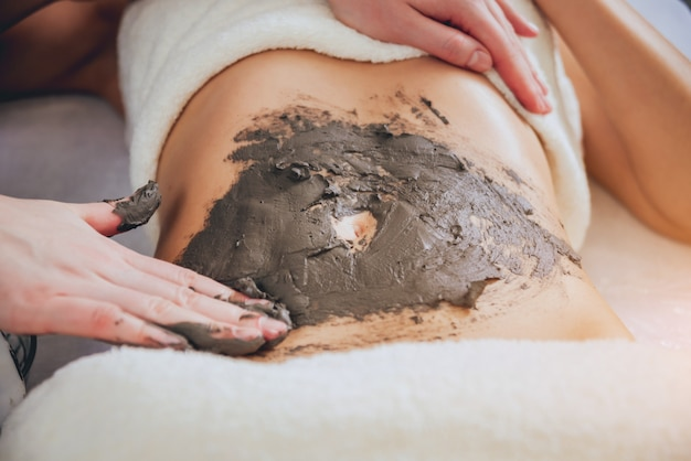 泥のボディマッサージを得るスパサロンで美しい女性