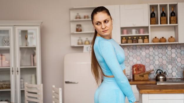 스포츠 유니폼에서 아름 다운 여자는 집에서 스포츠 훈련을 위해 준비 중입니다.
