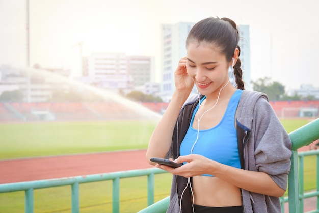 도시에서 야외에서 운동 후 이어폰에서 음악을 듣고 스포츠에서 아름 다운 여자. 야외에서 운동 후 이어폰에서 음악을 듣고 스포츠에서 아름 다운 아시아 여자.