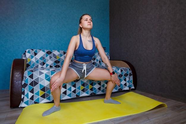 Красивая женщина в спортивной одежде, шортах и бюстгальтере, стоящая в позе плие, упражнения, привлекательная девушка, практикующая йогу, тренировка дома или в современной студии йоги, растяжка тела