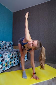 Красивая женщина в спортивной одежде, шортах и бюстгальтере, стоящая в позе, упражнения, привлекательная девушка, практикующая йогу, тренировка дома или в современной студии йоги, растяжка тела