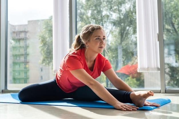 ヨガ、屋内で瞑想を練習するマットに座っているスポーツウェアの美しい女性