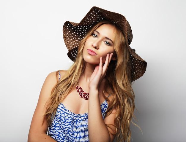 わらの夏の帽子の美しい女性