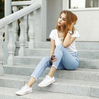 Красивая женщина в стильной одежде, сидя на крыльце возле дома.