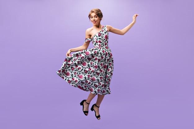 孤立した背景にジャンプするスタイリッシュな衣装の美しい女性。カラフルなモダンな服と黒い靴の笑顔でかなり若い女性。