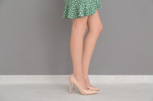 色の壁の近くのスタイリッシュな靴の美しい女性