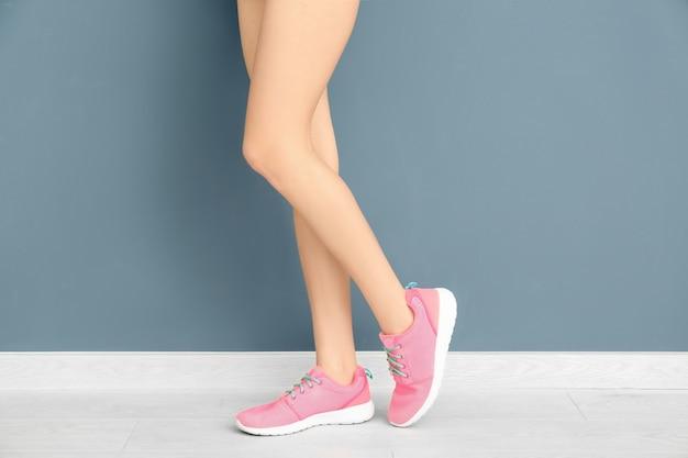 Красивая женщина в стильной обуви возле цветной стены
