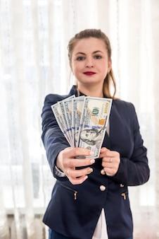 달러 지폐를 보여주는 한 벌에서 아름 다운 여자
